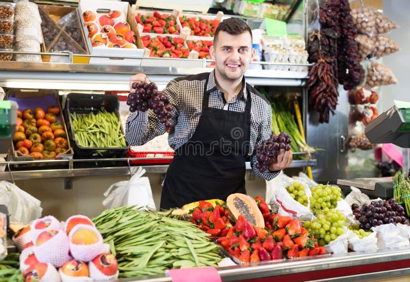 Froher männlicher Verkäufer, der Zusammenstellung des Lebensmittelgeschäfts zeigt stockfotografie