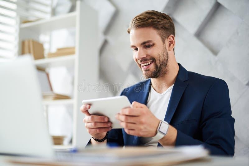 Froher Mann, der portative Gerät bei der Arbeit verwendet stockbild