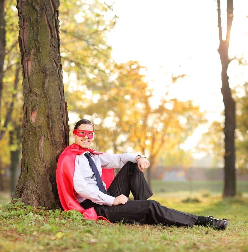 Froher Mann in der Superheldausstattung, die in einem Park sitzt stockfotos