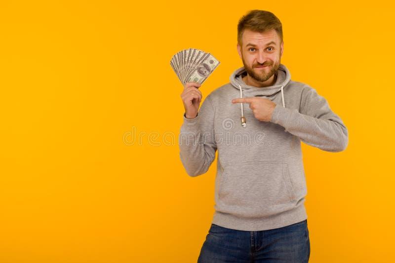 Froher Mann in einem grauen Hoodie zeigt einen Finger auf Gelddollar auf einem gelben Hintergrund stockfoto
