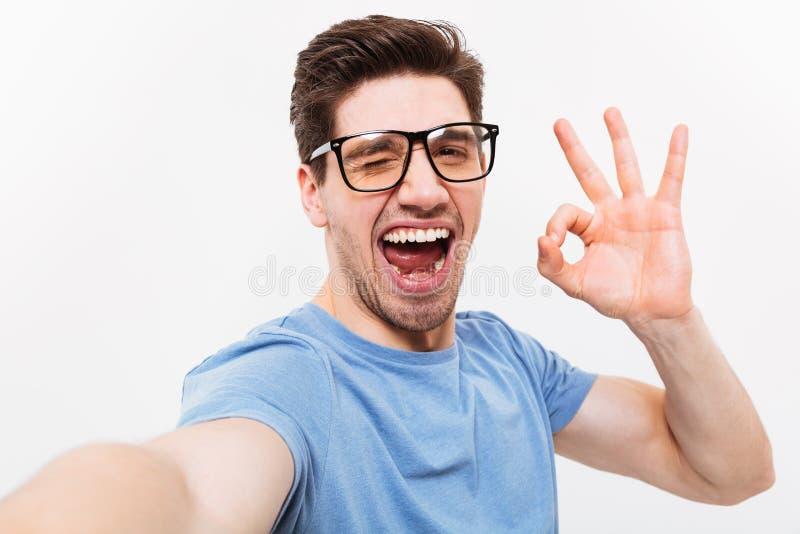 Froher Mann im T-Shirt und in Brillen, die selfie machen stockbild