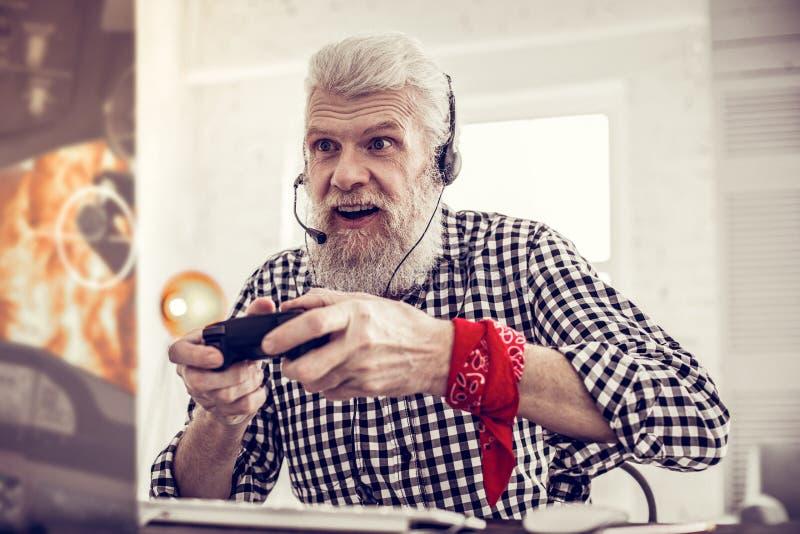 Froher reifer Mann, der Computerspiele mit Vergnügen spielt stockfotos