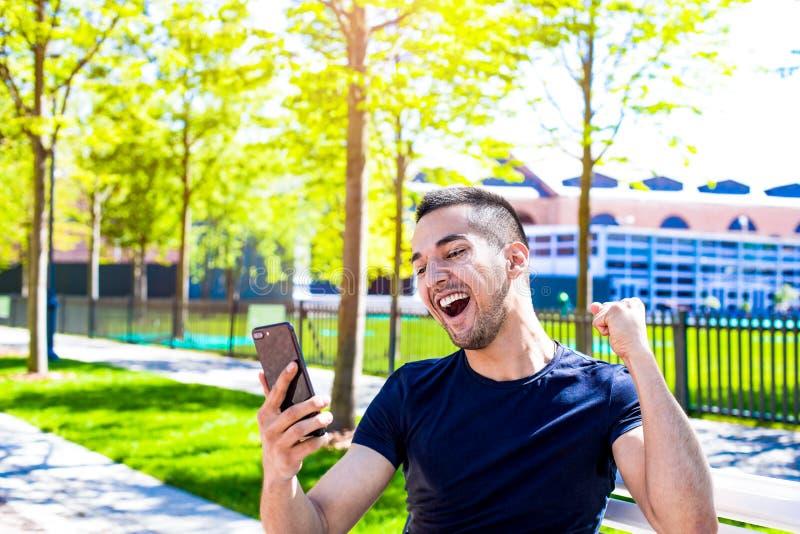 Froher Siegermann, der seinen Erfolg, Mobiltelefon halten sich freut Männlich, Videoanruf über zelluläres habend stockfoto
