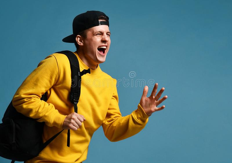 Froher Student des jungen Mannes mit Läufen eines Rucksacks lokalisiert im Studio auf einem purpurroten Hintergrund lizenzfreies stockbild