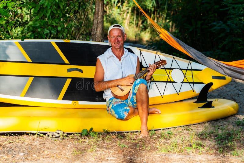 Froher Supsurfer entspannt sich in einem Flusskampieren lizenzfreies stockfoto