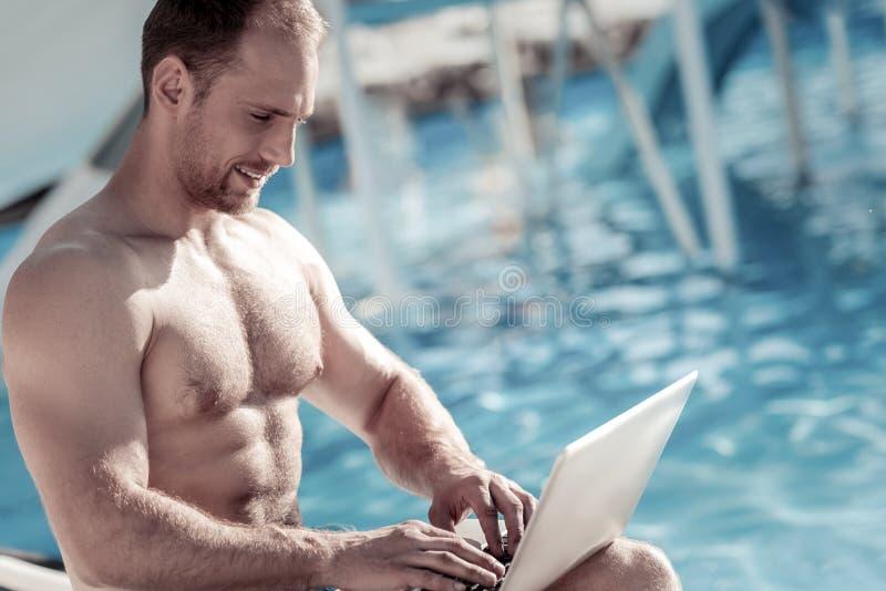 Froher tausendjähriger Kerl, der an Laptop am Pool arbeitet stockfotos