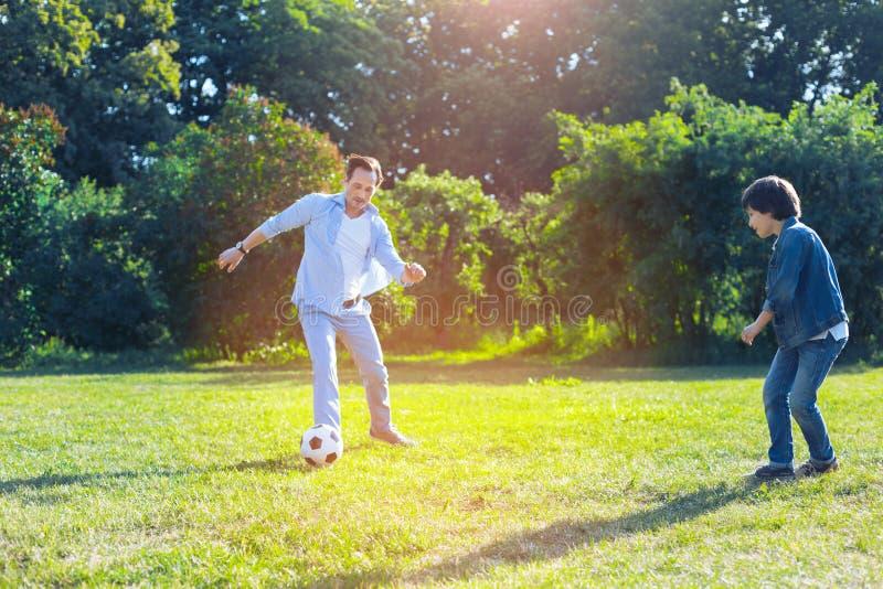 Froher Vater und Sohn, die zusammen Fußball spielt lizenzfreie stockbilder