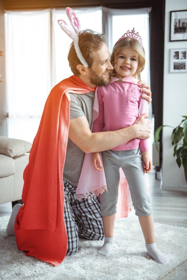 Froher Vati, der kleine Tochter mit Vorliebe umarmt lizenzfreie stockbilder