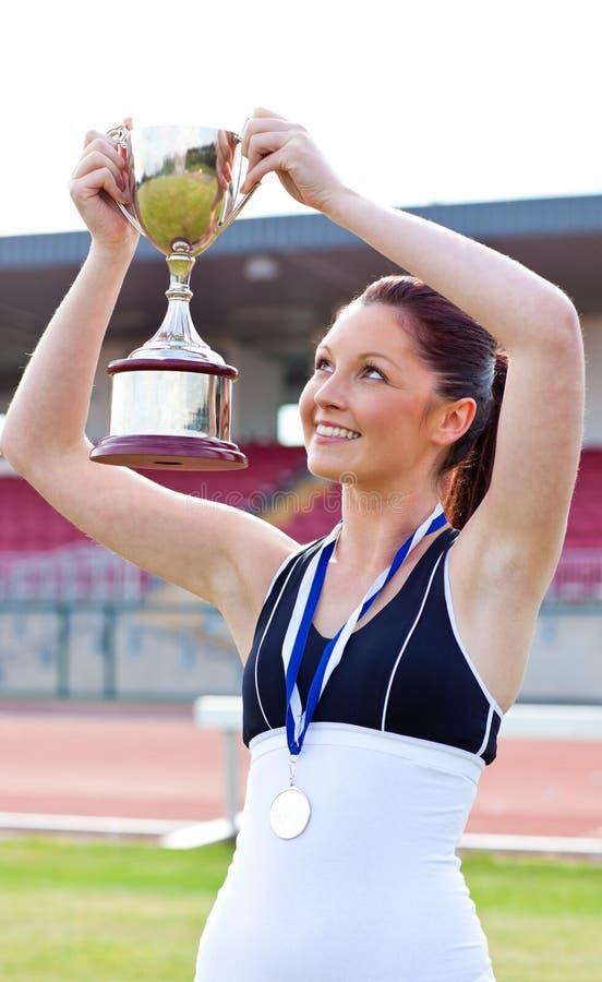 Froher weiblicher Athlet, der eine Trophäe und eine Medaille anhält lizenzfreie stockfotografie