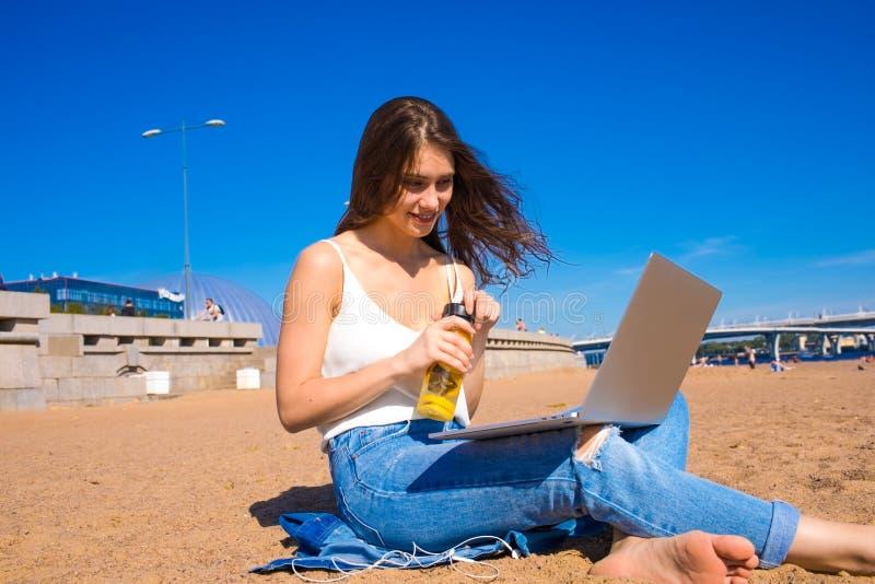 Froher weiblicher Bloggerleseartikel auf Webseite über die Laptop-Computer, sitzend auf Küstenlinie lizenzfreie stockfotos
