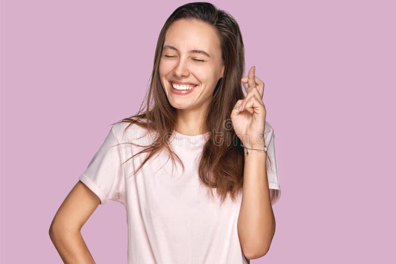 Frohes abergläubisches junges Mädchen in den Schauspielen kreuzt Finger, betet vor wichtiger Gelegenheit, wünscht Glück, Hoffnung stockfoto