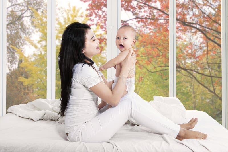 Frohes Baby und Mutter im Schlafzimmer lizenzfreies stockbild