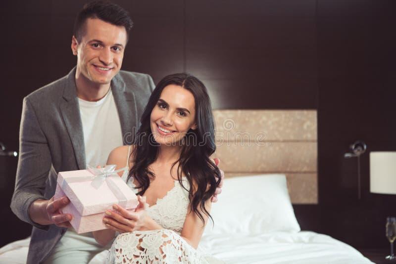 Frohes Bräutigamgeben seiner liebevollen Braut vorhanden lizenzfreies stockfoto
