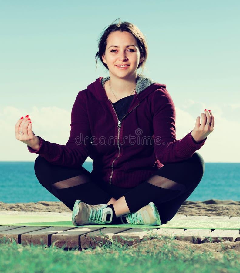 Frohes erwachsenes Mädchen, das auf Übungsmatte trainiert stockbild