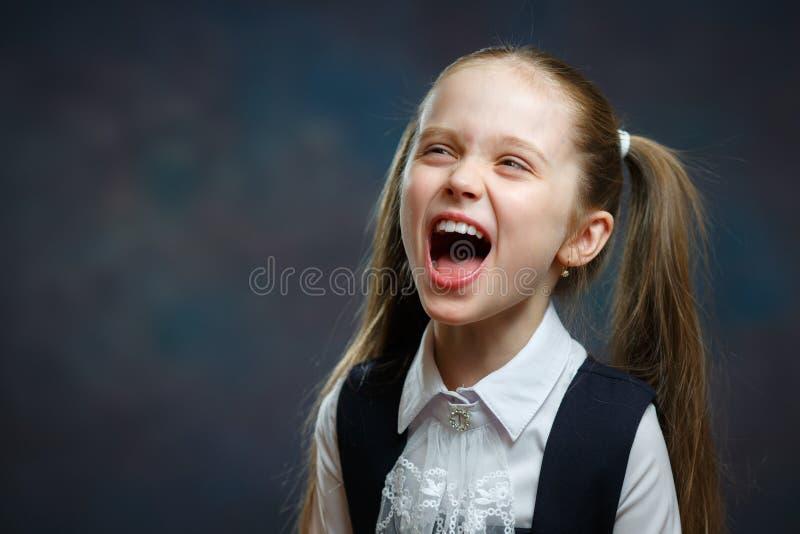 Frohes grundlegendes Schulmädchen-emotionales Porträt stockfotos