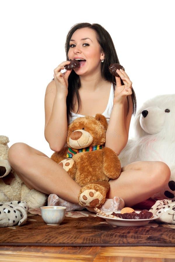 Frohes hübsches Mädchen, das Schokoladenbiskuit isst lizenzfreie stockfotografie