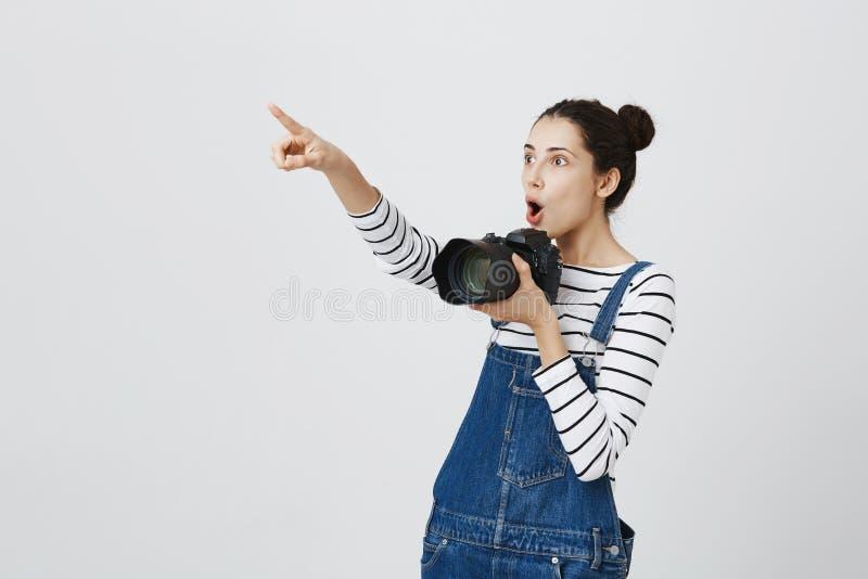 Frohes Hippie-Mädchen mit hairbuns in der modischen Kleidung herum gehend während der Exkursion, aufpassende lokale Kuriositäten: lizenzfreie stockfotos