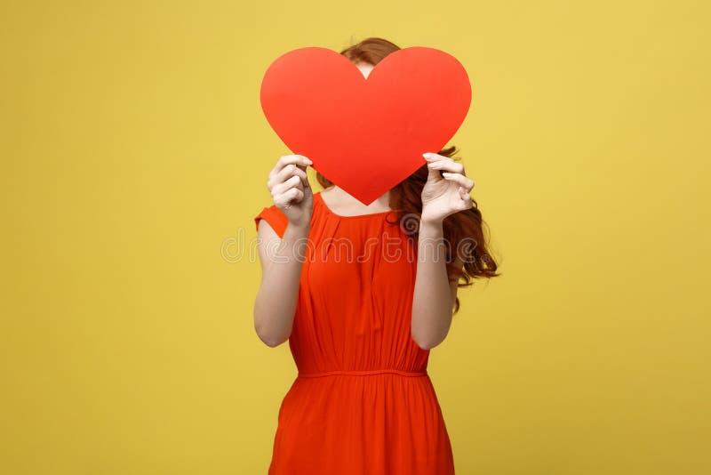 Frohes kaukasisches Mädchen im orange herrlichen Kleid, das rotes Herz hält, bedecken ihr Gesicht Flache Schärfentiefe Liebevolle stockbilder