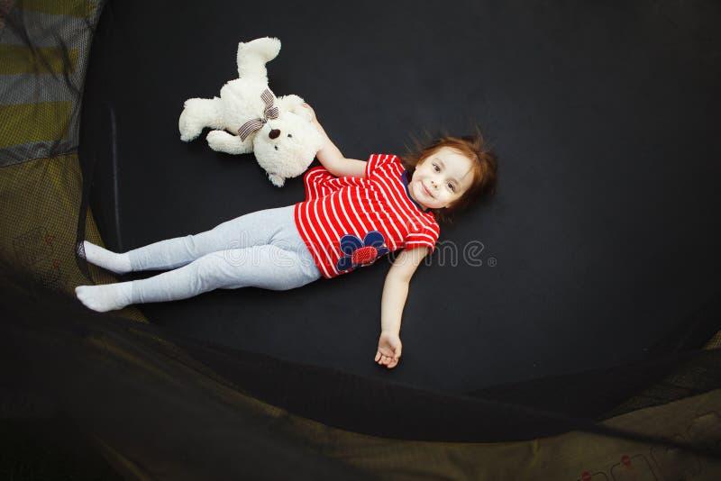 Frohes Kind in der Trampoline mit weichem Spielzeug lizenzfreies stockfoto