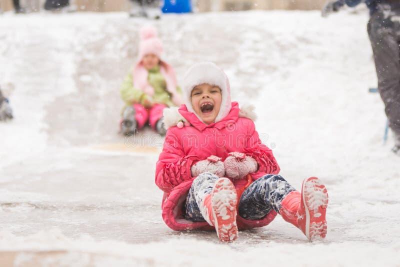 Frohes Kind rollt Dias eines siebenjährige Eises stockfoto