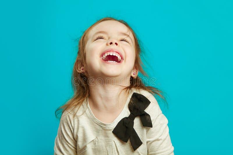 Frohes kleines Mädchen lacht auf blauem Hintergrund lizenzfreie stockfotografie