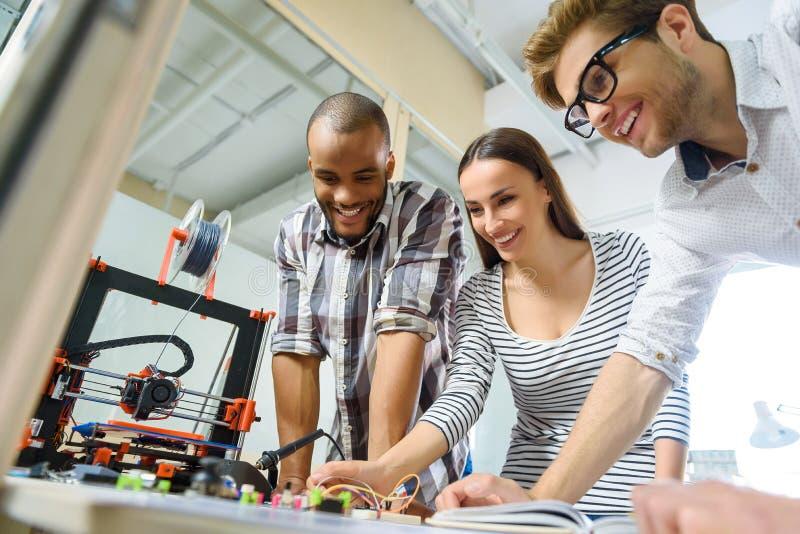 Frohes kreatives Team, das mit dreidimensionaler Technologie arbeitet lizenzfreies stockbild