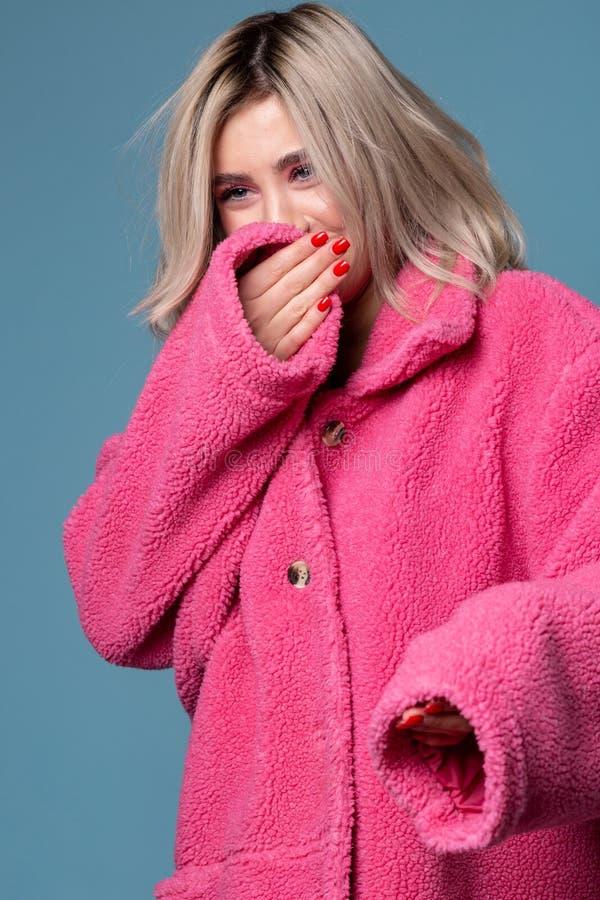 Frohes lächelndes blondes weibliches Modell, das ihr Gesicht hinter Hand versteckt stockfotografie