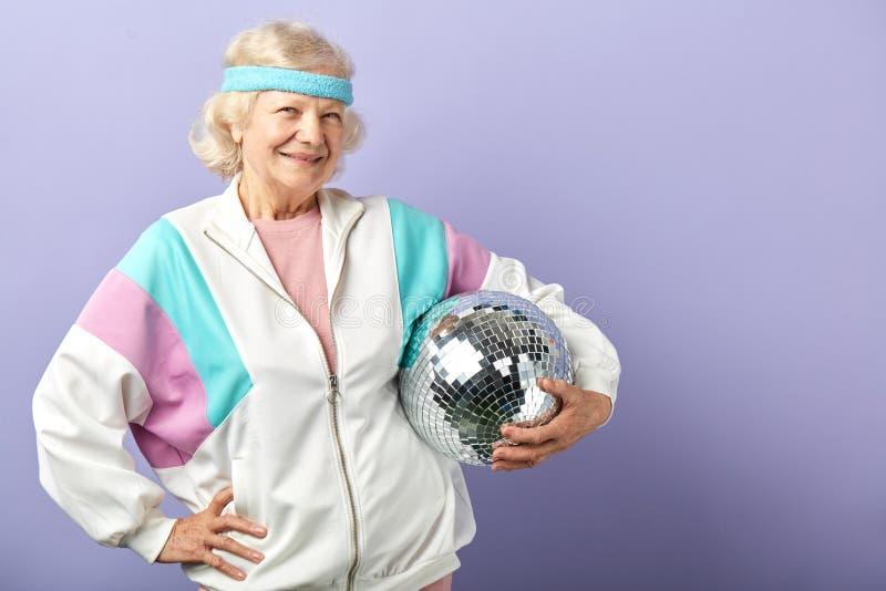 Frohes l?chelndes Greisinportr?t gekleidet in der Sportkleidung, mirrow Ball halten stockfotografie