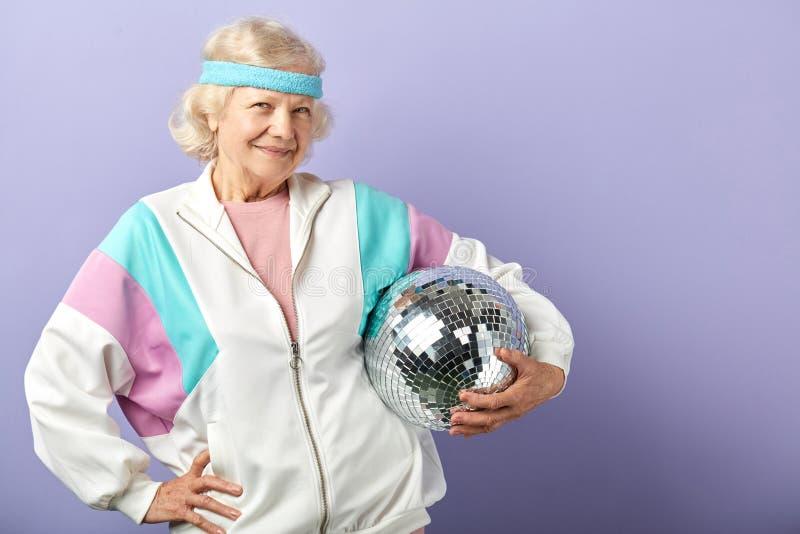 Frohes l?chelndes Greisinportr?t gekleidet in der Sportkleidung, mirrow Ball halten stockbilder