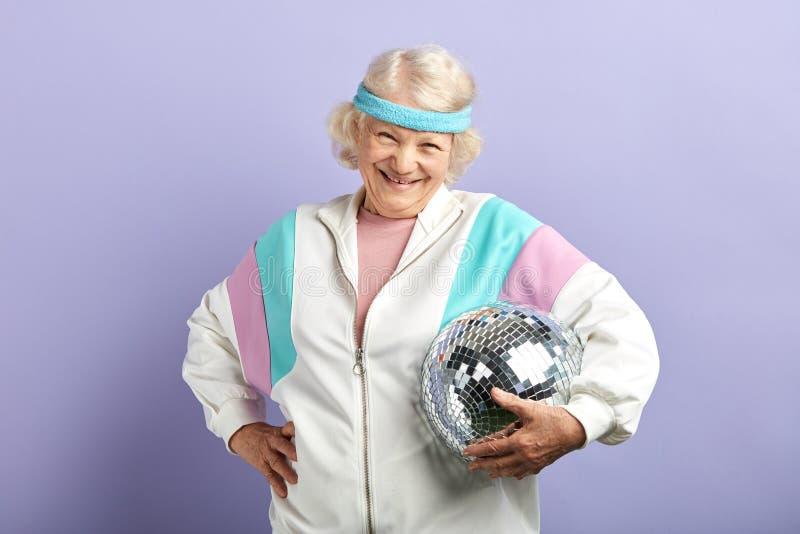 Frohes l?chelndes Greisinportr?t gekleidet in der Sportkleidung, mirrow Ball halten lizenzfreie stockbilder