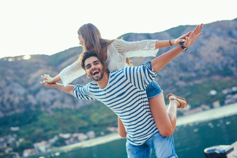 Frohes Mädchen, das auf jungem Freund huckepack trägt stockfoto