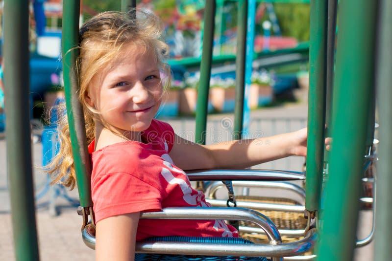 Frohes Mädchen fährt auf ein Karussell und betrachtet die Kamera lizenzfreie stockfotografie