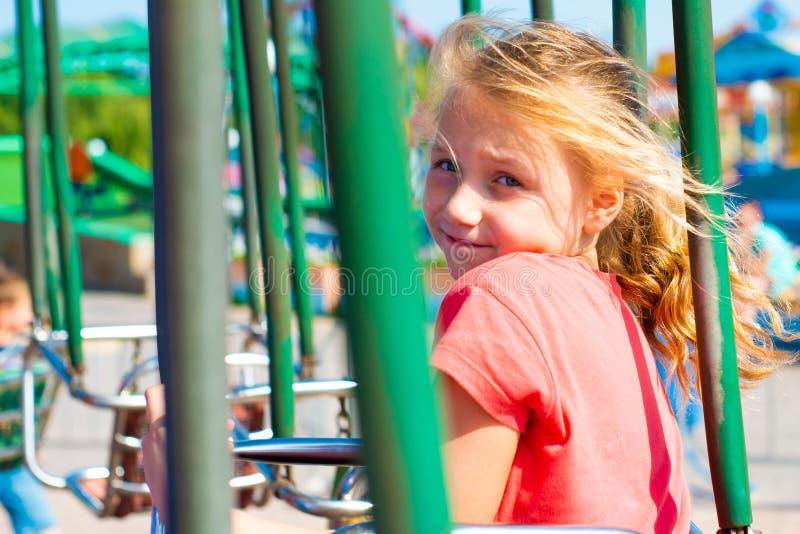 Frohes Mädchen fährt auf ein Karussell und betrachtet die Kamera stockbild