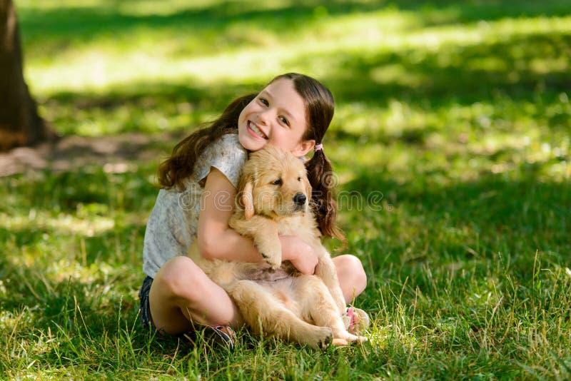 Frohes Mädchen umfasst ihr Haustier stockbild