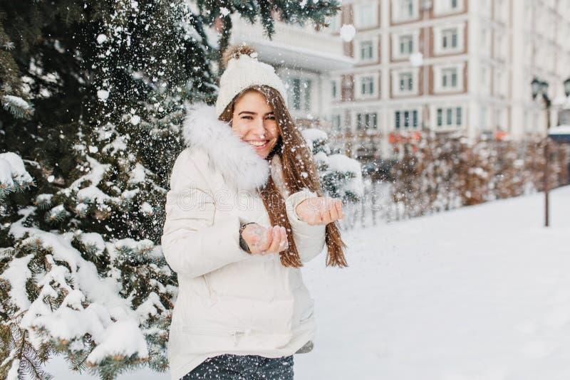 Frohes nettes Mädchen, das Spaß mit den snowlakes im Freien auf dem Tannenbaum voll mit Schneehintergrund hat Junges reizend Mode lizenzfreie stockfotografie