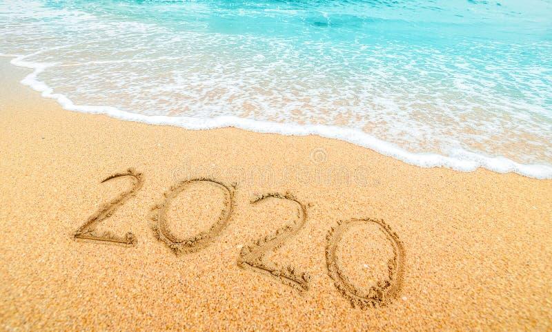 Frohes neues Jahr 2020, Schreiben am Strand mit Welle und blauem Meer Zahlen 2020 Jahr an der Küste, Neujahrskonzept stockfotos