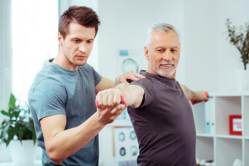 Frohes positives Manntraining mit einem Trainer lizenzfreie stockfotografie