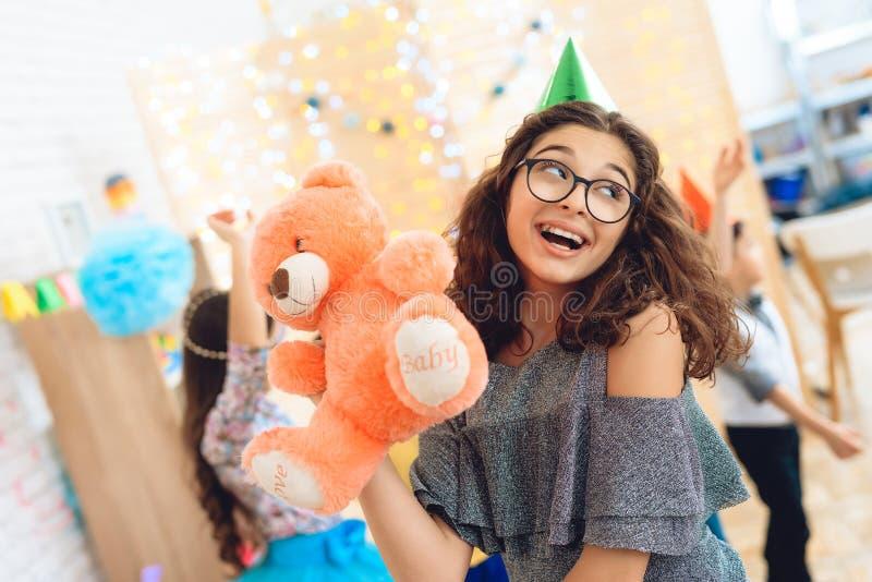 Frohes schönes Mädchen im grünen festlichen Hut wird mit Teddybären betreffen Geburtstagsfeiertag gefallen lizenzfreie stockfotografie