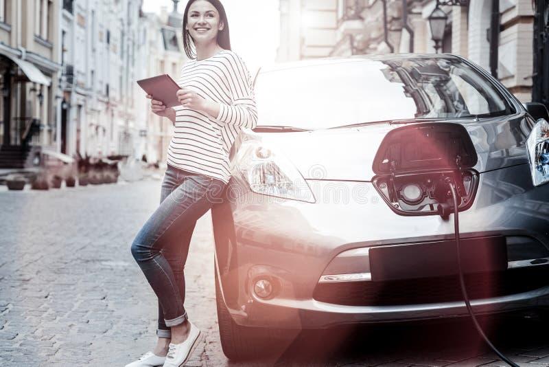 Frohes tausendjähriges Mädchen, das Tablette bei der Aufladung ihres Elektroautos verwendet lizenzfreie stockbilder