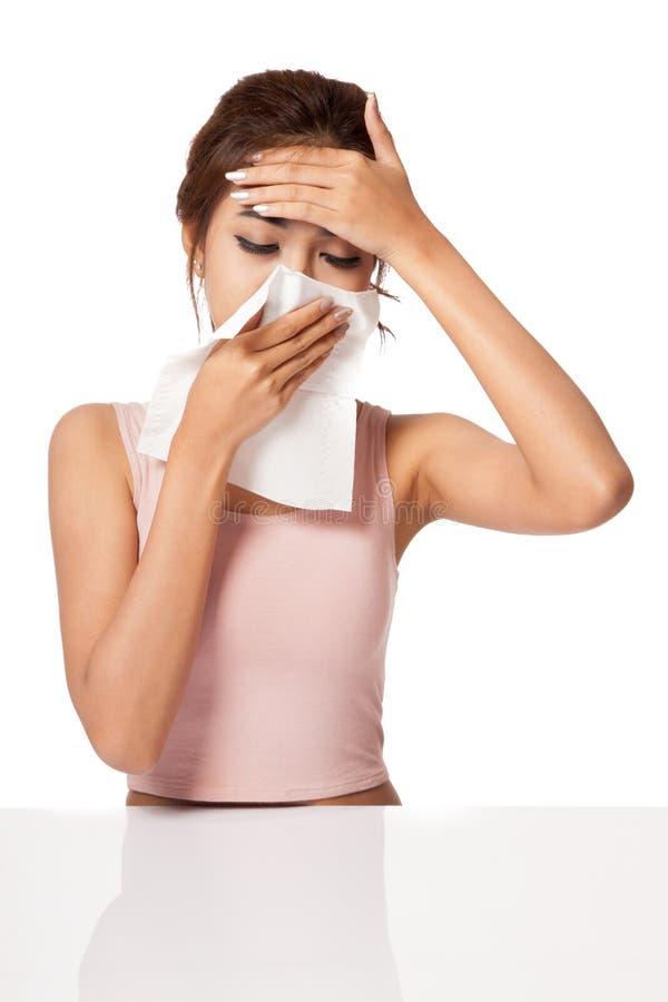 Froid attrapé par fille assez asiatique Éternuement dans le tissu photo stock