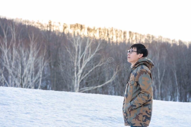 Froid de port d'homme bel, vêtements de port d'hiver parmi les pins avec la neige couverte pour se sentir seul, seul photographie stock
