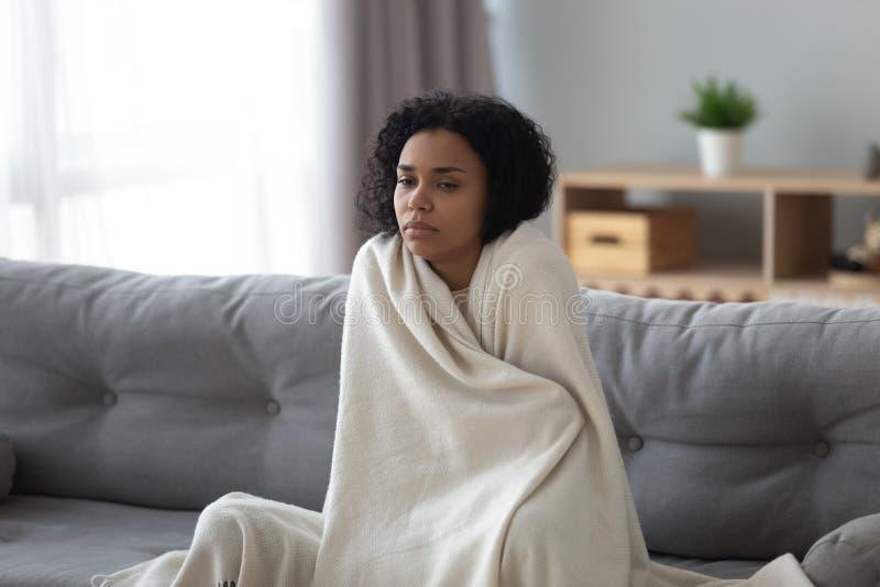 Froid se sentant de femme africaine malade couvert de couverture à la maison image libre de droits