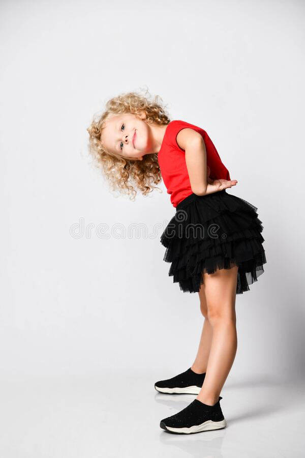 Free Frolic Curly Hair Blonde Kid Girl In Red T-shirt And Black Skirt Stands Side To Us Bending With Her Hands At Her Waist Stock Image - 178403891