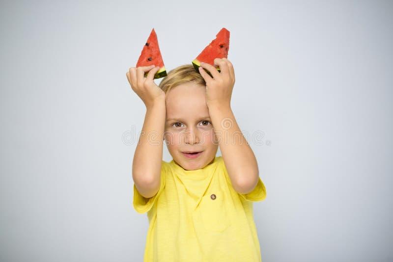 Frolicsome årigt pojkebarn för caucasian 5 i den gula t-skjortan som rymmer två stycken av den röda vattenmelon ovanför hans huvu royaltyfri fotografi