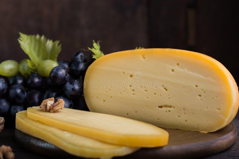 Fromage à pâte dure néerlandais Maasdam ou Emmental, fromage avec des trous et fromage de chèvre dur blanc Fromage entier, slisec images stock