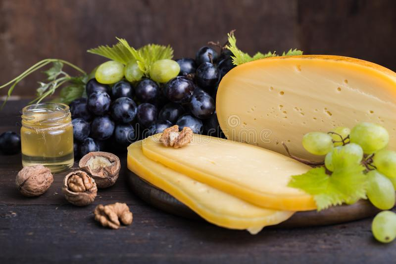 Fromage à pâte dure néerlandais Maasdam ou Emmental, fromage avec des trous et fromage de chèvre dur blanc Fromage entier, slisec image stock