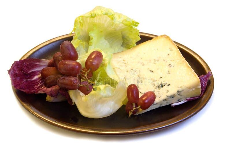 Fromage à veines bleues avec des raisins et la salade photos stock