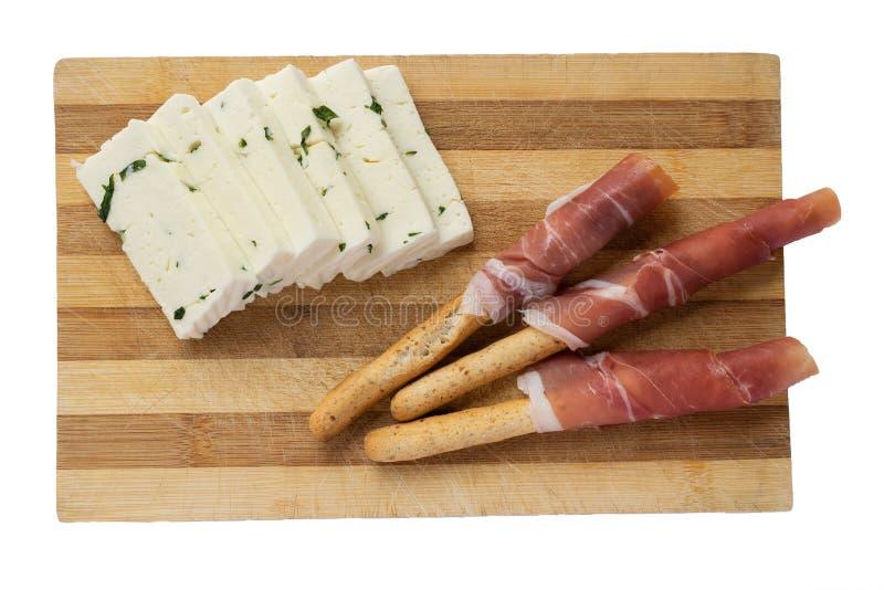 Fromage avec des verts et gressins avec le prosciutto sur un conseil en bois images libres de droits