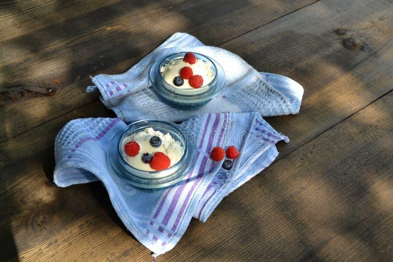 Fromage blanc avec les framboises et les myrtilles fraîches dans le bol en verre sur le fond noir en bois Dessert doux Nutrition  photos libres de droits
