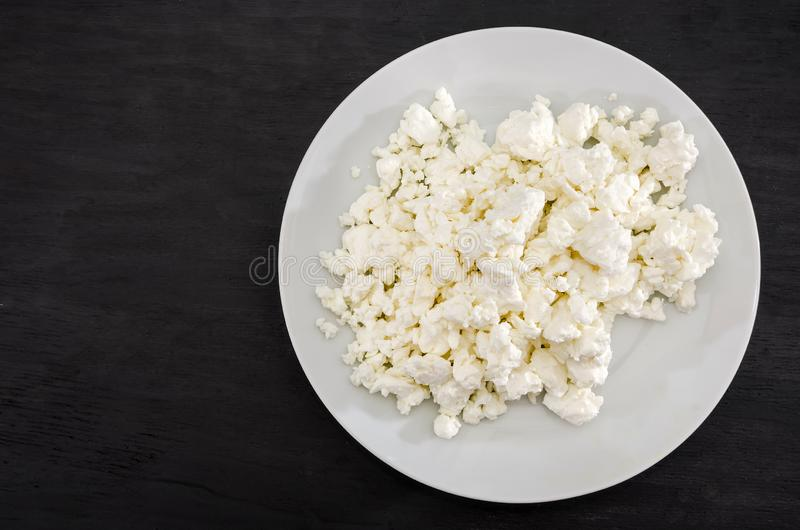 Fromage blanc cottage dans une assiette blanche sur une table noire Placer le texte Vue depuis le haut photo stock